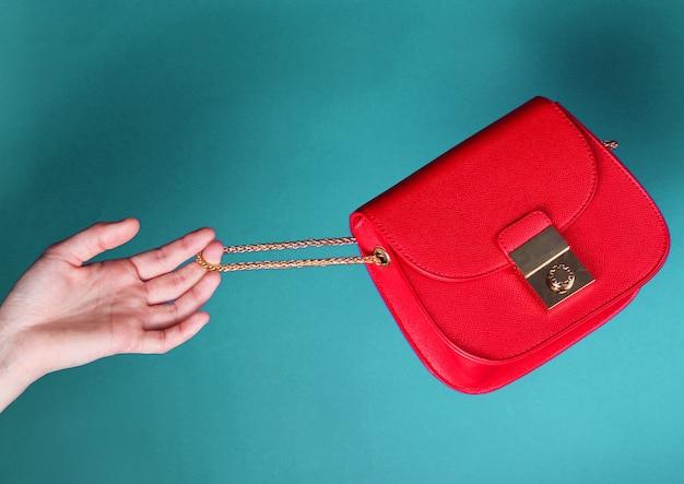 女性の手は青い背景に金色のチェーンとファッショナブルな赤い革のバッグを保持します。