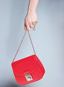 女性の手は灰色の背景に金色のチェーンとファッショナブルな赤い革のバッグを保持します。