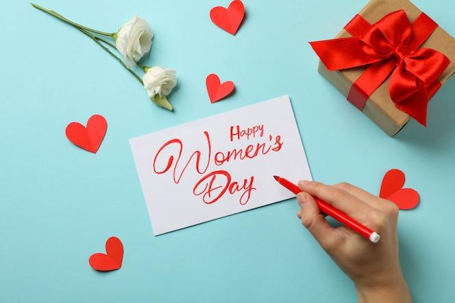 feltro della stretta della mano femminile - pennarello, testo happy women's day, confezione regalo, rose e cuori su sfondo blu