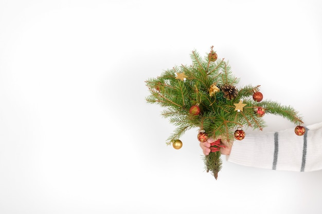 Female hand hold a festive christmas bouquet of spruce