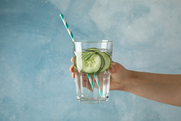 女性の手は青い表面に対してキュウリの水のガラスを保持します。