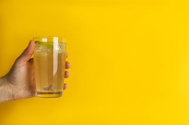 女性の手は黄色の背景にジンジャービールのガラスを保持します。