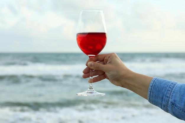 海に対して女性の手はグラスワインを保持します