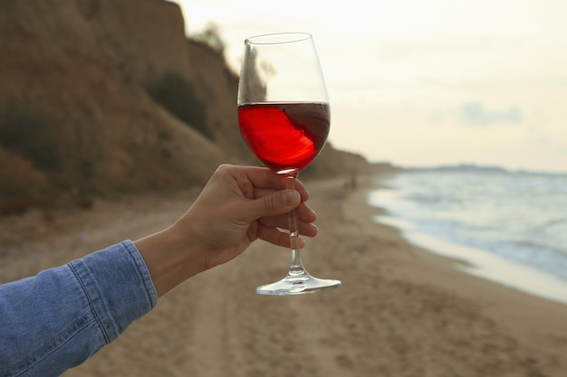 女性の手は砂浜でワインのグラスを保持します