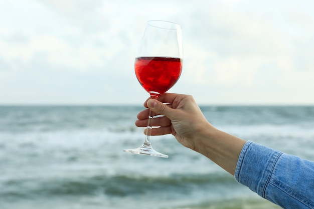 Female hand hold glass of wine against sea