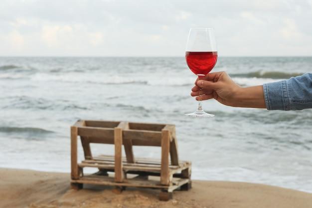 Female hand hold glass of wine on sandy beach