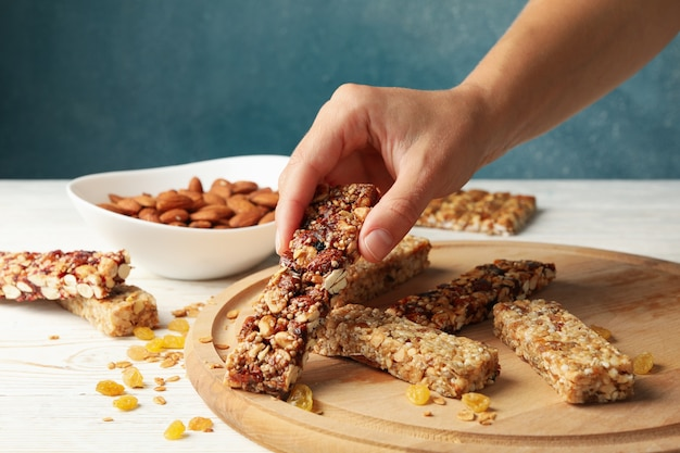 Female hand hold granola bar on wooden background with granola bars