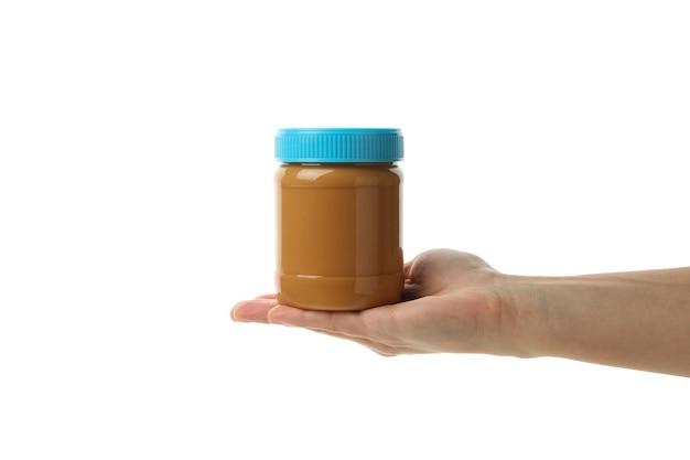 Женская рука держит банку с арахисовым маслом, изолированную на белом фоне