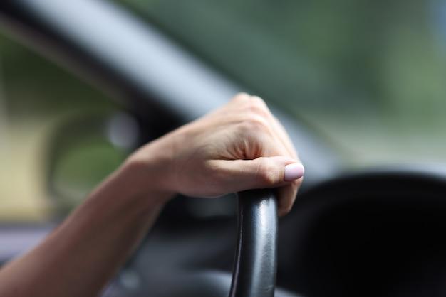 車の中で女性の手は革のハンドルを握る