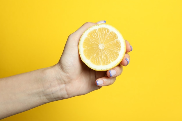 Female hand hold lemon on yellow background