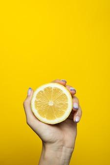 Female hand hold lemon on yellow wall