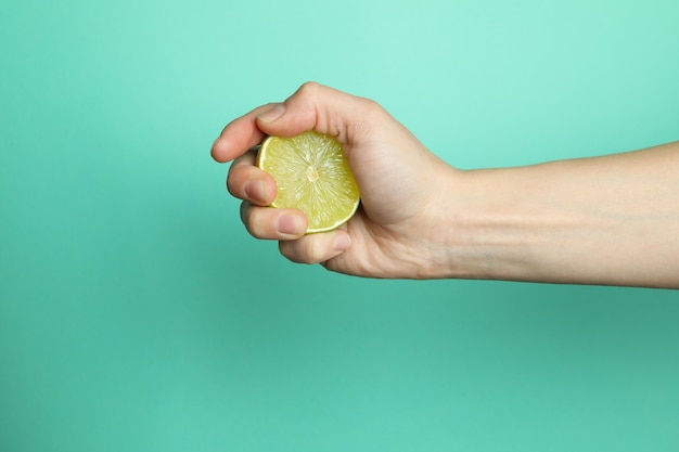 Female hand hold lime on mint wall