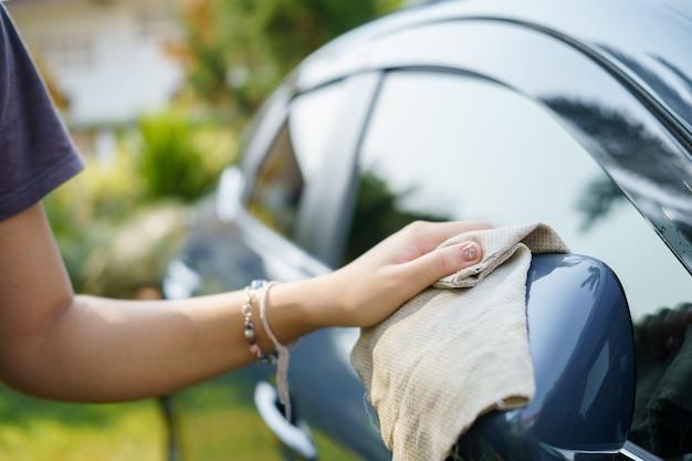 車を洗うための女性の手持ちマイクロファイバークロス。コンセプト消毒と消毒洗浄