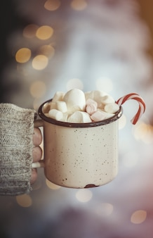 Female hand hold mug of coffee with candy cane and marshmallows