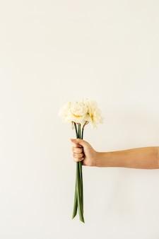 Женская рука держит букет цветов нарцисса на белой поверхности