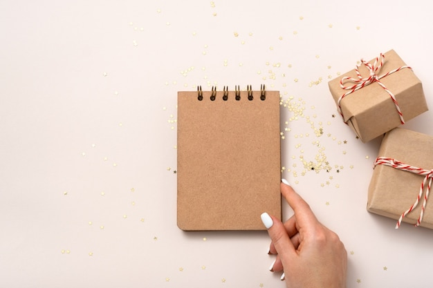 Female hand hold notebook blank paper mockup, golden stars confetti, gift boxes on beige background. flat lay, top view, copy space, minimalist. christmas new year composition.