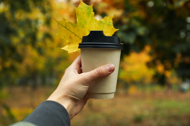 Female hand hold paper cup on autumn park background