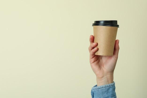 Женская рука держит бумажный стаканчик на бежевой поверхности