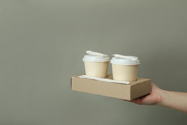 Женская рука держит бумажные стаканчики на серой поверхности