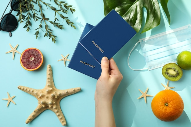 Female hand hold passports on blue isolated background with summer accessories with mask