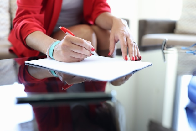 女性の手はペンを保持し、契約書に署名します。