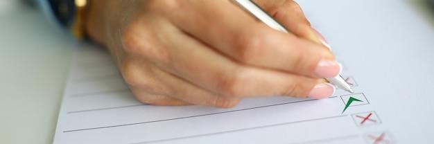 Женская рука держать ручку в руке крупным планом и писать.