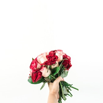 Female hand hold pink and red rose flowers bouquet isolated on white