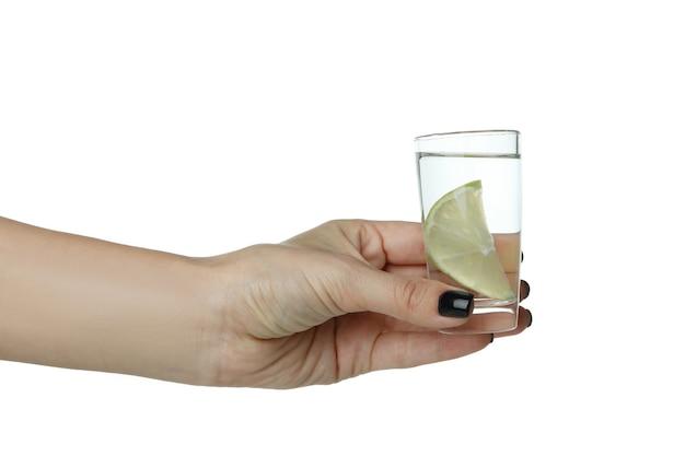 Женская рука держит рюмку водки или текилы с лаймом, изолированной на белой поверхности