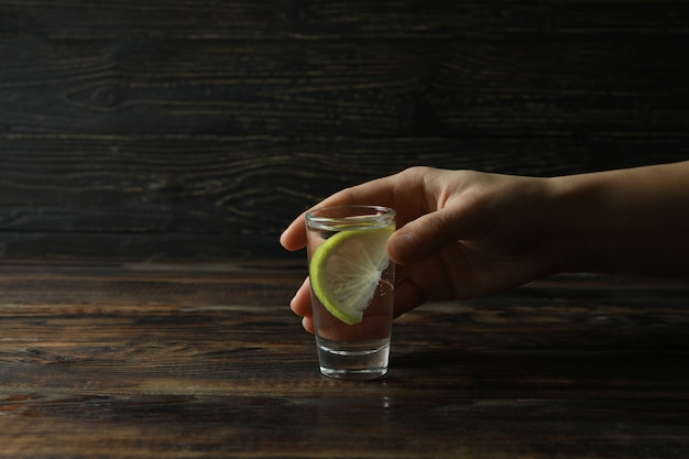 Female hand hold shot of vodka or tequila with lime on wooden table