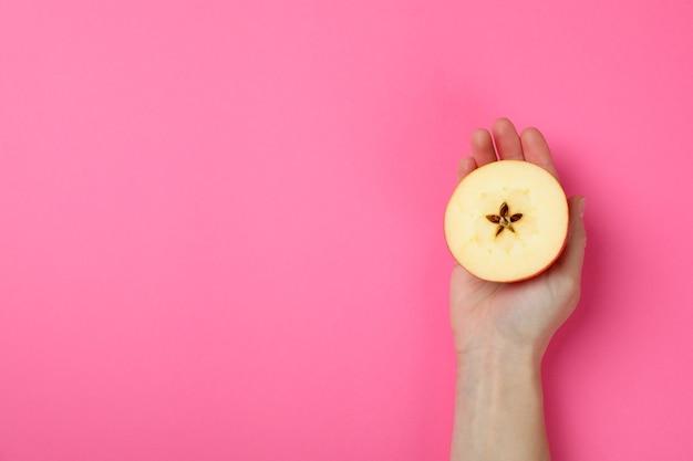 여성의 손을 잡고 분홍색 배경에 애플 슬라이스
