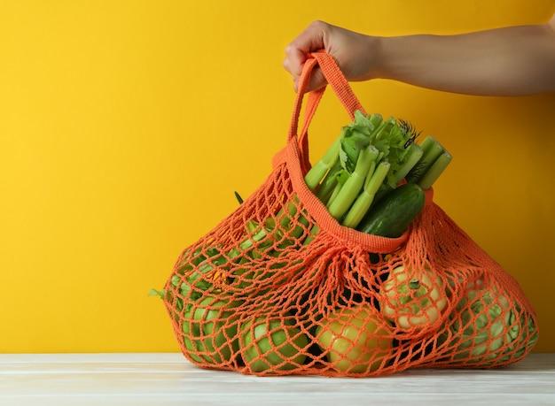 女性の手は黄色の背景に緑の食べ物と文字列バッグを保持します。