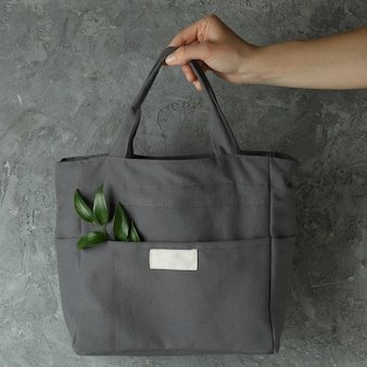 Female hand hold stylish eco bag with twig against gray textured background