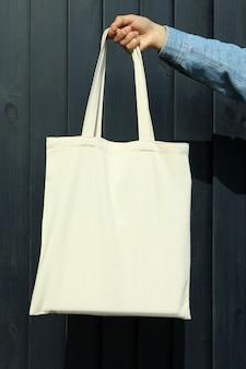 Female hand hold stylish eco bag on wooden background
