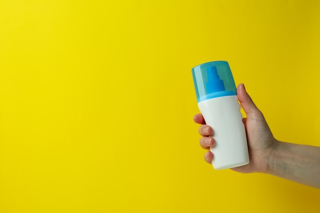 Female hand hold sunscreen on yellow isolated background