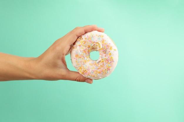 Female hand hold tasty donut on mint background