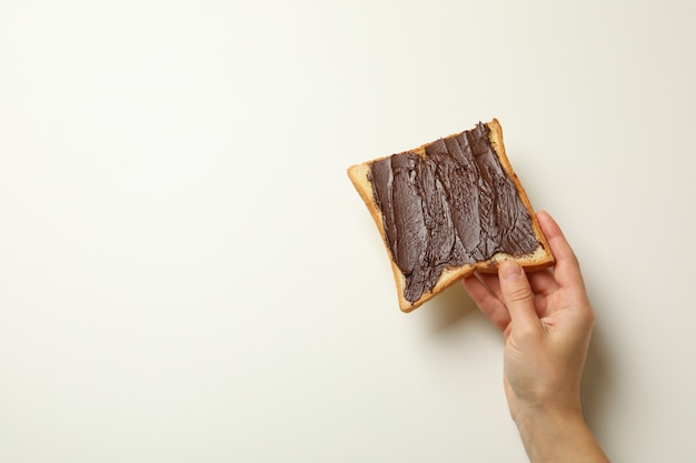 Female hand hold toast with chocolate on white