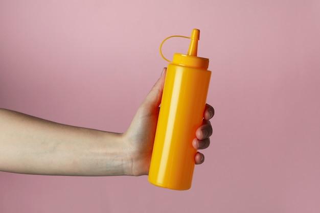 女性の手はピンクの孤立した背景に黄色のソースボトルを保持します。