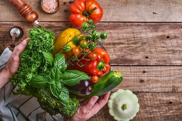 古い木製の素朴な背景、上面図に新鮮な野菜や果物のバスケットを持っている女性の手。テキスト用のスペース。料理の背景とモックアップ。