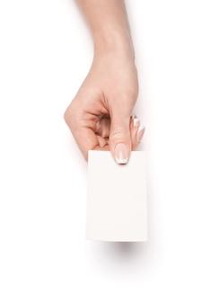 白い表面上に空白の名刺を持っている女性の手