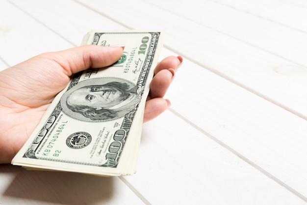 여성 손 나무 배경에 돈 다발을 들고. 100 달러 지폐의 투시도. 디자인을위한 빈 공간으로 급여 개념입니다.