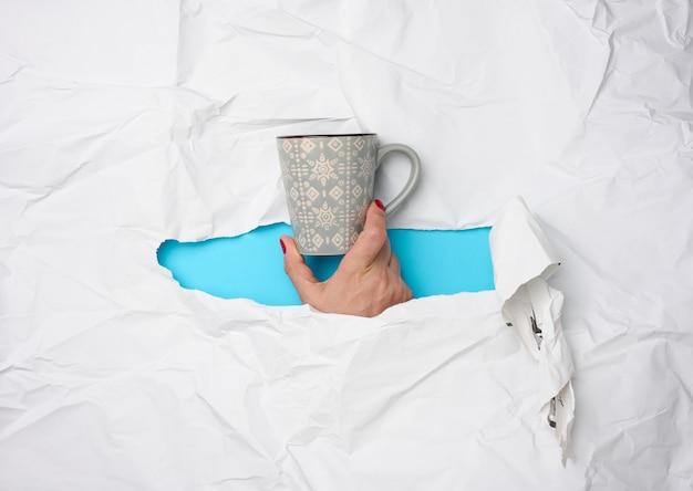 흰색 찢어진 종이 배경에 세라믹 머그를 들고 있는 여성 손, 커피를 마시고 휴식을 취하는 시간