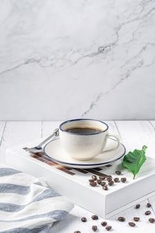 白い台所のテーブルにコーヒーカップを持っている女性の手。