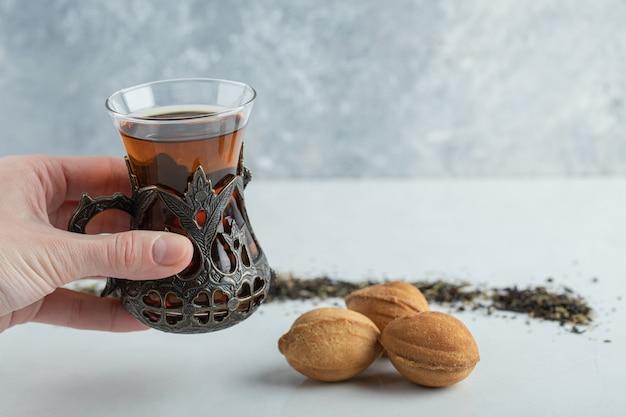 달콤한 호두 모양의 쿠키와 허브 차 한 잔을 들고 여성 손.