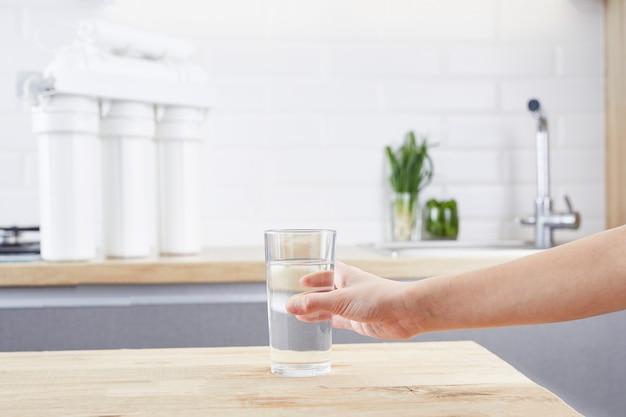きれいな水のガラスを持っている女性の手。浄化された水と健康的な生活の概念。
