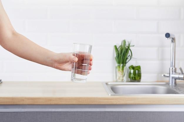 きれいな水のガラスを持っている女性の手。精製水と健康的な生活のコンセプトです。