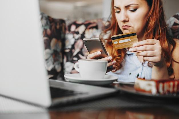 銀行からの画面にすぐに通知されなかった後、インターネットバンキングにアクセスしているときに金のクレジットカードとスマートフォンを持っている女性の手。