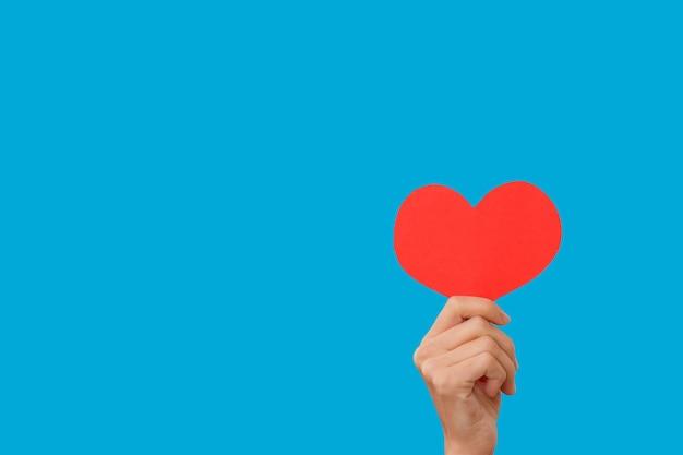 여성의 손을 잡고 심장-사랑의 상징, 고립 된 파란색 배경