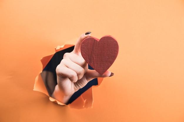 オレンジ色の背景にハートを持っている女性の手