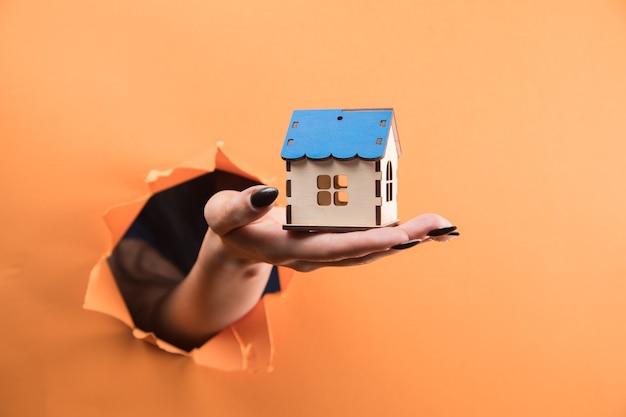 オレンジ色の背景に家を持っている女性の手