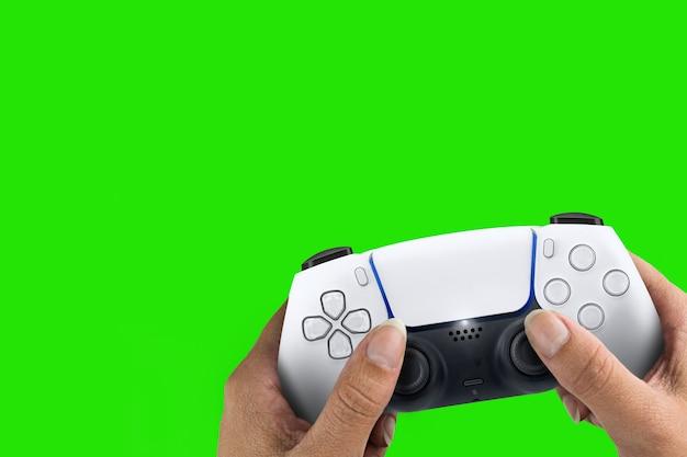 緑の画面の背景に分離された次世代の白いゲームコントローラーを持っている女性の手。クロマキー。